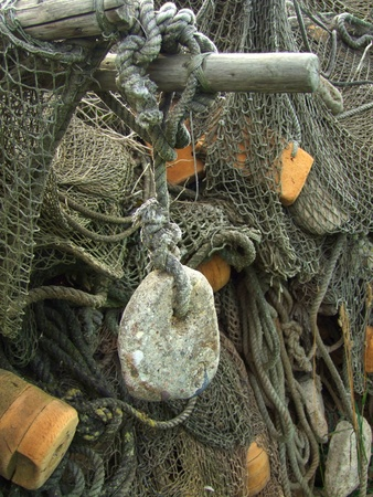 float and stone sinker, old fishing nets closeup photo