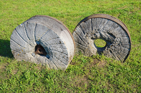 millstone: An ancient millstone were located on the grass in the natural background Stock Photo