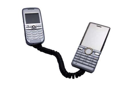 mobiele telefoons: twee mobiele telefoons verbinding telefoonsnoer Stockfoto