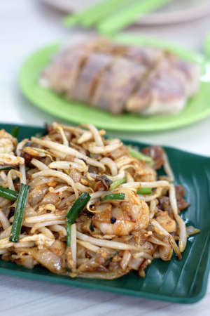 Hawker food of fried flat rice noodles and spring rolls on green plate
