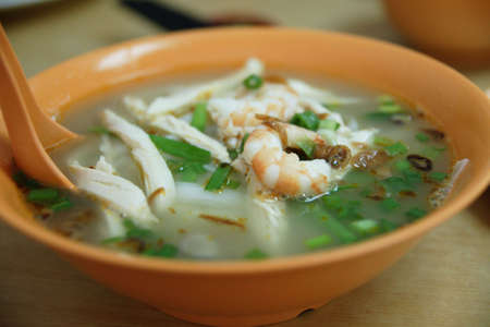 A bowl of Chinese flat noodles or koay teow with prawns and sliced chicken Stock Photo