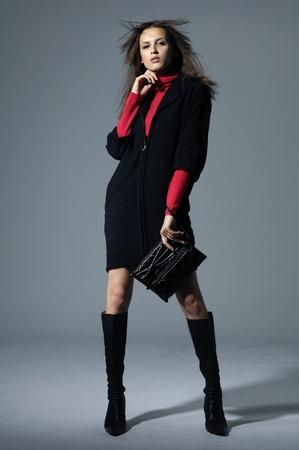 Vogue style photo of fashion model holding little purse