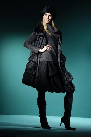 Fashion model in winter dress on blue light studio Stock Photo