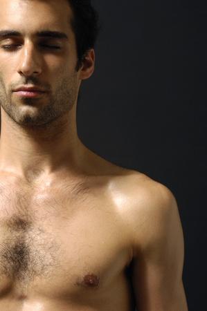 Close up young sensual man on a black