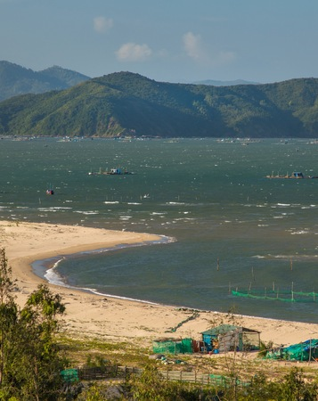 shrimp boat: The coastline beach and shrimp farming rigs in Vung Lam Bay Vietnam looking over the south China sea. Stock Photo