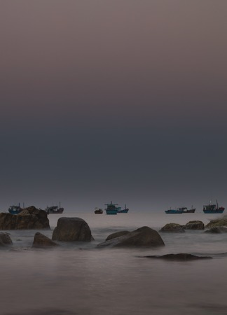 aisa: A rocky coastline morning glow looking out over the south China sea in Vung Lam Bay Vietnam. With rock and fishing boat silhouettes.