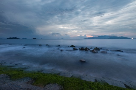 A moody morning sky over Nha Trang bay Vietnam just before sunrise with moss covered rocks in the foreground. Editorial