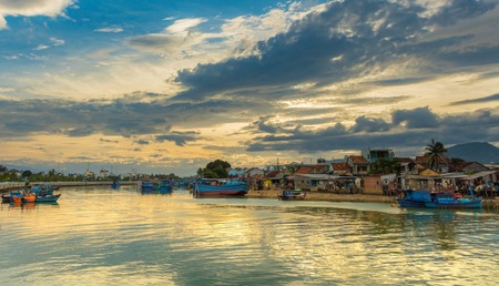 Vietnamese fishing boats on the cai river used as a harbour with a cloudy sunset sky Nha Trang Vietnam.