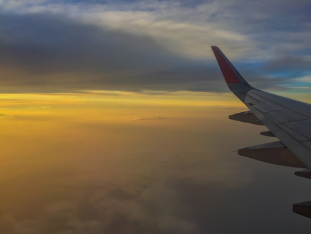 High altitude in flight passenger jet airliner airplane wing, with a cloudy sunset colourful sky.