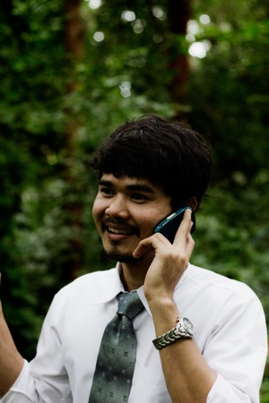 a businessman with a mobile phone in a forest photo