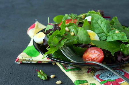 Fresh green salad with cherry tomatoes pine nuts and quail eggs. Salad dressing. Healthy eating. The concept