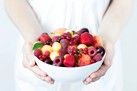 Different berries in a bowl in the hands of the girls. Healthy and snack