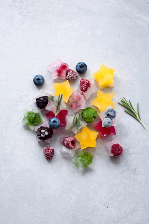 Ice cubes with berries and herbs in the form of a star