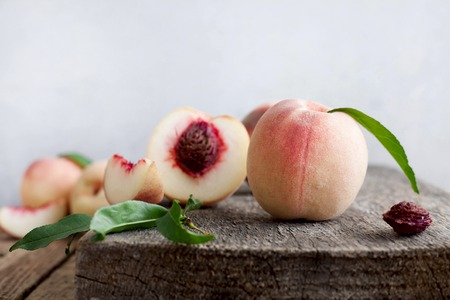 Peaches on wooden background with leaves