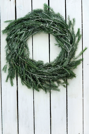 Christmas wreath of tree branches on wooden background