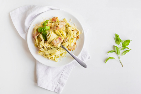 Pasta with avocado, bacon and Basil on a white background