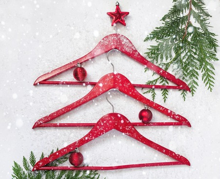 Christmas tree made of clothes hangers decorated with Christmas toys on white background with tree branches in the snow. Foto de archivo