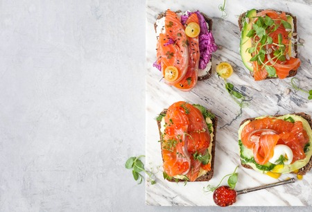 Smorrebrod with salmon on rye bread with vegetables, herbs, microsaint, red caviar and quail egg