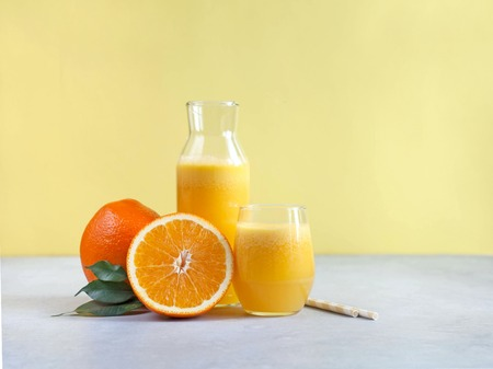 Freshly squeezed orange juice on a yellow background. Copy space