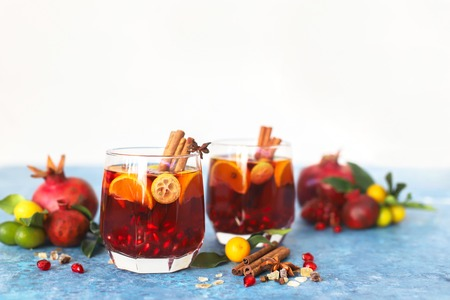 Bunch of drinks made of Sangria pomegranate, pear, orange, kumquat and spices, cinnamon, cloves, star anise on a table Stock Photo