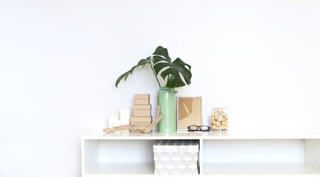 Cozy Interior of the living room. Shelf with a vase with monstera leaves, frame, candles, glasses, various design elements.