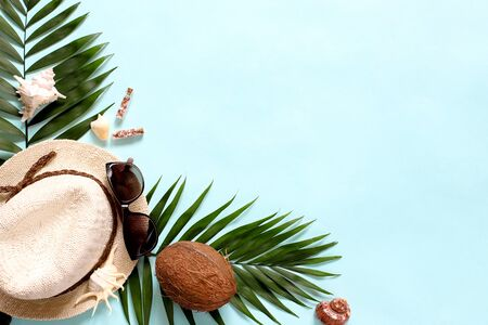 Summer, tropical turquoise background with a straw hat, coconut, sunglasses. Monstera leaves and palm trees, sea shells .