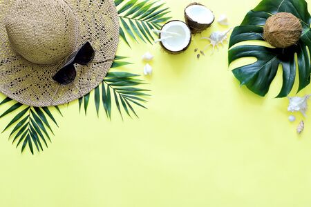 Summer, tropical yellow background with a straw hat, coconut, sunglasses. Monstera leaves and palm trees, sea shells .