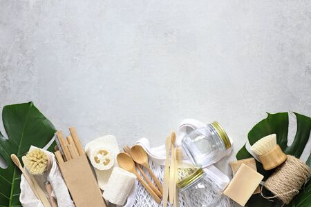 Items made of natural materials. The concept of zero waste. Natural bamboo toothbrush, drinking tube, natural sponge, on a gray background with monstera leaves. Flat layout, top view, space for copying.