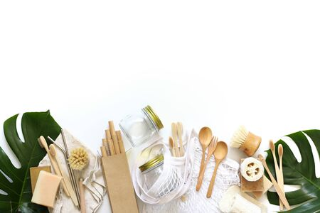 Items made of natural materials. The concept of zero waste. Natural bamboo toothbrush, drinking tube, natural sponge, on a white background with monstera leaves. Flat layout, top view, space for copying.