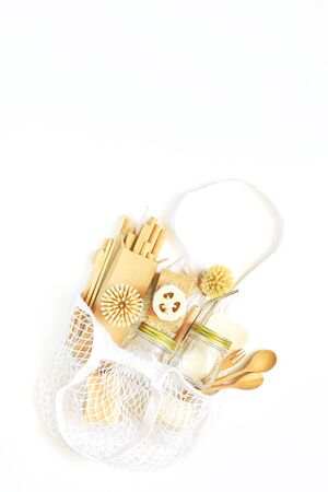 Bag string bag with items made of natural materials. The concept of zero waste. Natural bamboo toothbrush, drinking tube, natural sponge, on a white background. Flat layout, top view, space for copying. 版權商用圖片