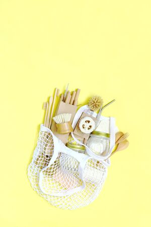 Bag string bag with items made of natural materials. The concept of zero waste. Natural bamboo toothbrush, drinking tube, natural sponge, on a yellow background.  Flat layout, top view, space for copying.