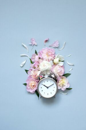 Creative minimalistic composition with a Clock. Alarm clock with peony flowers. Spring time. Time to love. Top view. On a blue background