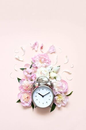 Creative minimalistic composition with a Clock. Alarm clock with peony flowers. Spring time. Time to love. Top view. On a pink background