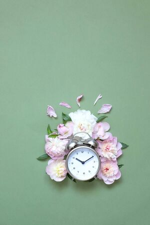 Creative minimalistic composition with a Clock. Alarm clock with peony flowers. Spring time. Time to love. Top view. On a green background 版權商用圖片