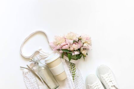Bag string bag with peony flowers, reusable thermocup, vacuum Cup,  glass bottle, metal tubes, white sneakers. The zero waste concept. The view from the top, a place for a label