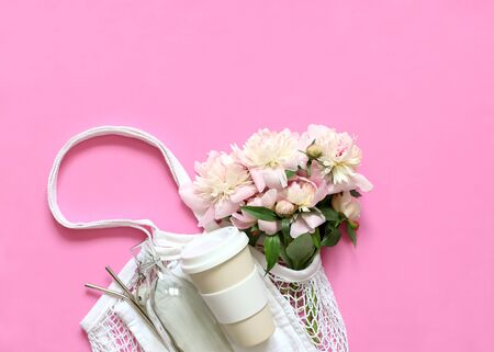 Tote bag with flowers peonies, reusable travel mug, vacuum Cup to the glass bottle, a metal tube on a pink background. The zero waste concept. The view from the top, place the graphic.
