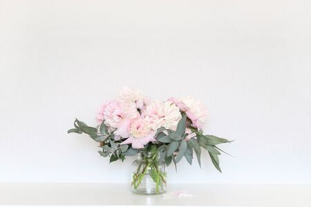 Peonies in the interior on the table.