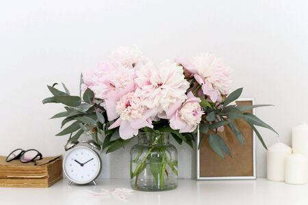 Peonies in the interior on the table, clock alarm clock, craft boxes, candles