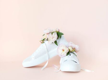 White sneakers on a pink background with peony flowers. Time of summer, time of love.