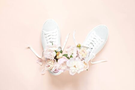 White sneakers on a pink background with peony flowers. Time of summer, time of love. Top view