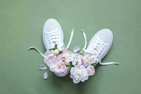 White sneakers on a green background with peony flowers. Time of summer, time of love. Top  view