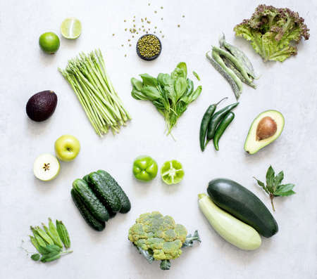 Farm organic vegetables and fruits on a white background are arranged by color. Top view.