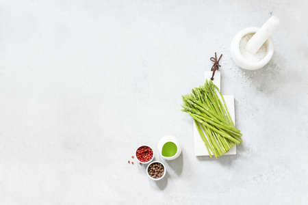 Fresh asparagus on a marble Board with spices and a marble white mortar with salt. Top view