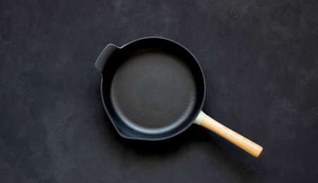 Cast iron frying pan with wooden handle on black background. The view from the top Standard-Bild