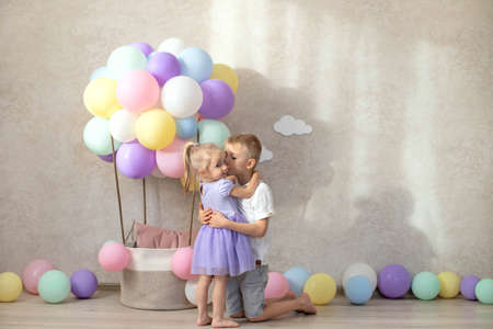 Decorative balloon basket, birthday 2 years old. The brother wishes his sister a happy birthday. Natural light, sun rays.