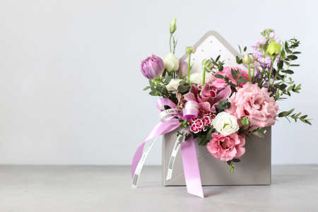 Festive composition, congratulations on the International Women's Day on March 8, Mother's Day, Valentine's Day, wedding day. An original bouquet of flowers made of tulips, orchids, eustoma, eucalyptus sprigs on a gray table. Standard-Bild