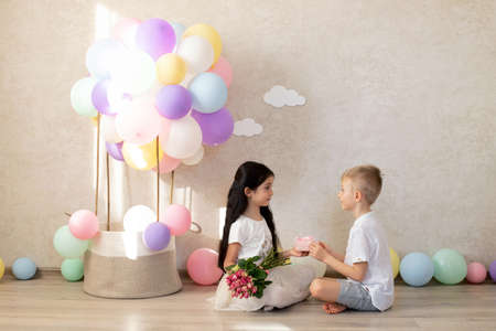 A boy child congratulates a girl child on a holiday. Valentine's Day, International Women's Day, March 8, birthday. The children's room is decorated with colorful balloons and a decorative basket of balloons. The boy gives a bouquet of flowers and a gift.