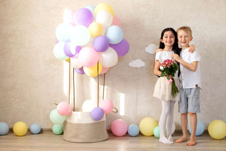 The boy congratulates the girl on the holiday, gives a bouquet of flowers and a gift. St. Peter's Day Valentine's day, March 8, birthday. The children's room is decorated with colorful balloons and a decorative basket of balloons.