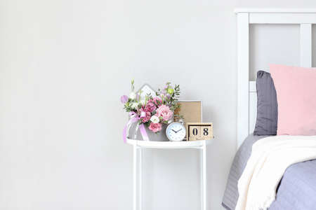 A bouquet of flowers for a woman on the bedside table on the day of the holiday on March 8, St. Valentine's Day, Mother's day, wedding day, birthday. Flower arrangement, photo frame, alarm clock.