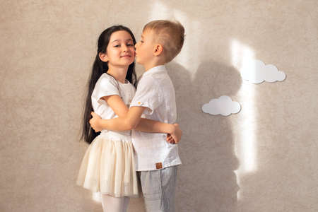 Portrait of a boy and a girl child laughing and hugging against the background of a wall with clouds and sunlight. Friends are children's emotions. Toothless smiles.